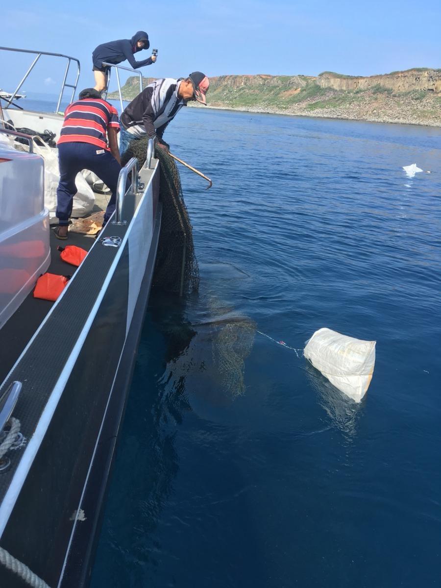 潛水人員於海底定位 再由船上人員協助撈起廢棄漁網漁具。國立高雄科技大學/提供
