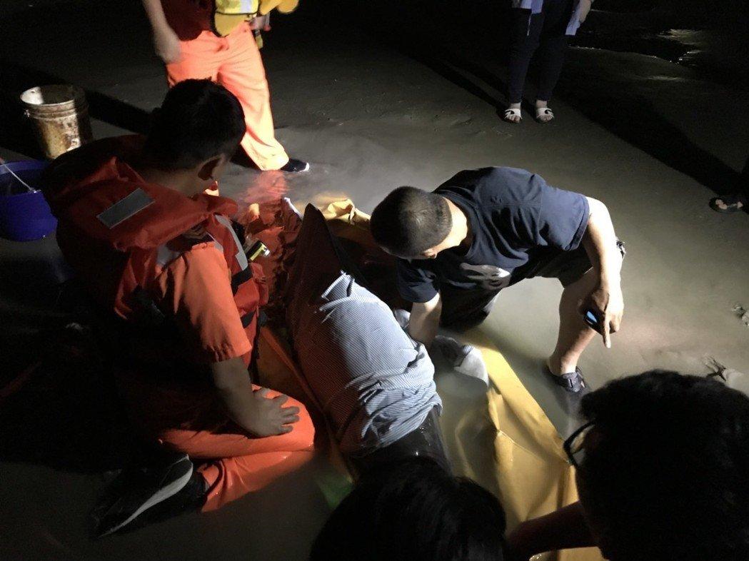 海巡人員與中華鯨豚協會徹夜照顧擱淺的糙齒海豚。海巡署中部分署第三岸巡隊/提供